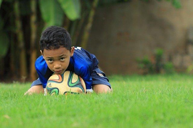 malý kluk ležící na fotbalovém míči